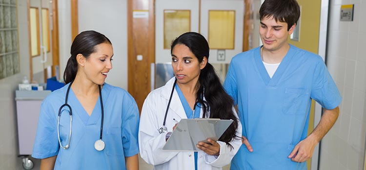 Nurses and a doctor walking in a hallway in a hospital
